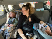 Mom sits in backseat of a car with newborn and older kid