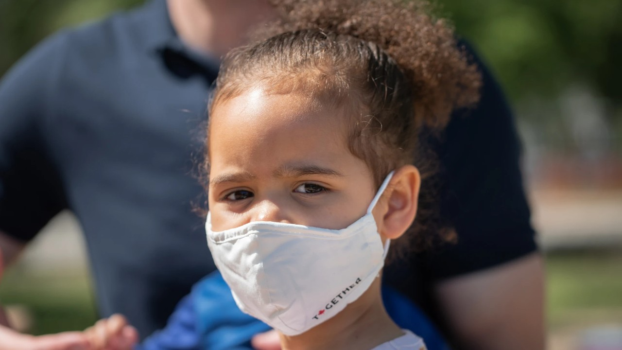 small girl wearing a white mask