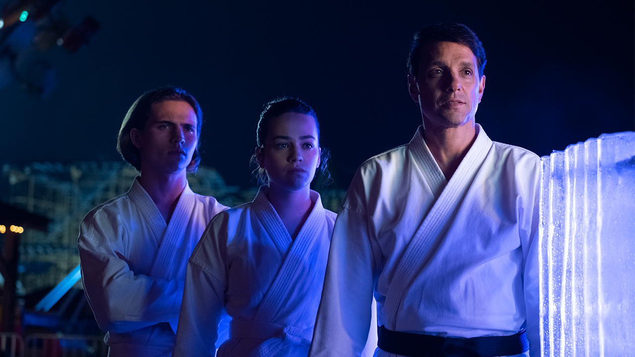 two teens stand with their karate instructor