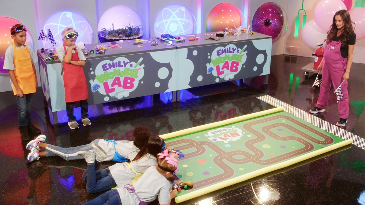 kids preparing to race toy cars in a science experiment
