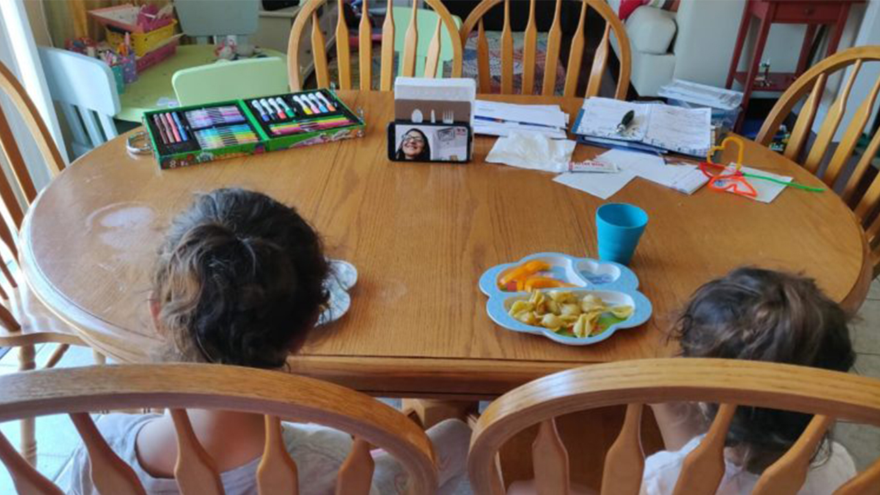 Photo of two kids sitting at the ktichen table eating while video chatting with a grown up on a phone