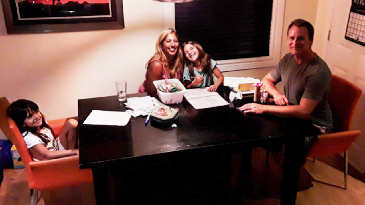 Photo of a family sitting at the family table