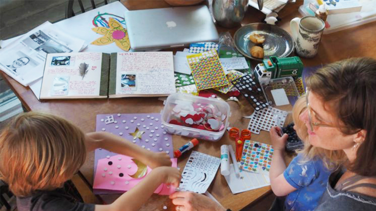 Photo of a mom and her kids crafting on the kitchen table