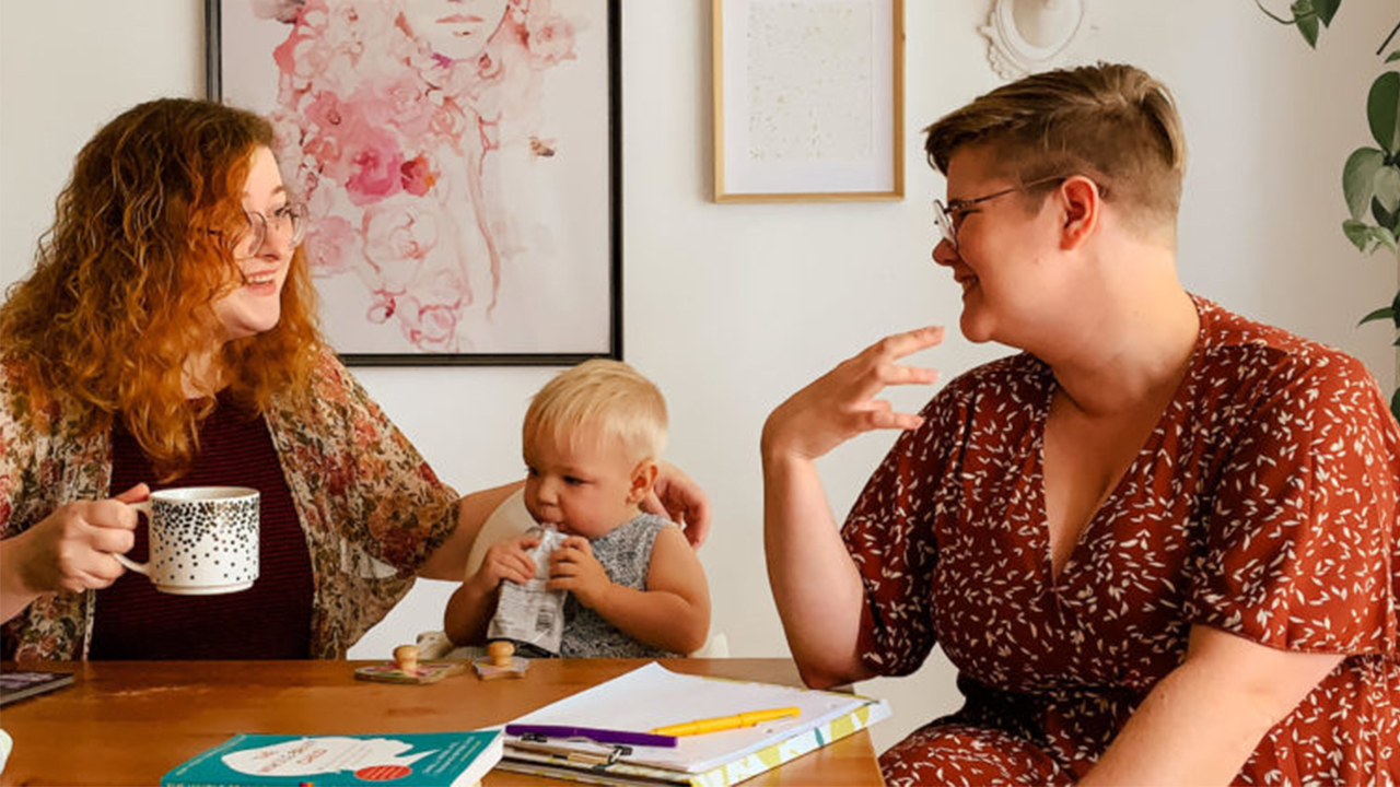 Photo of moms and a toddler sitting at the kitchen table