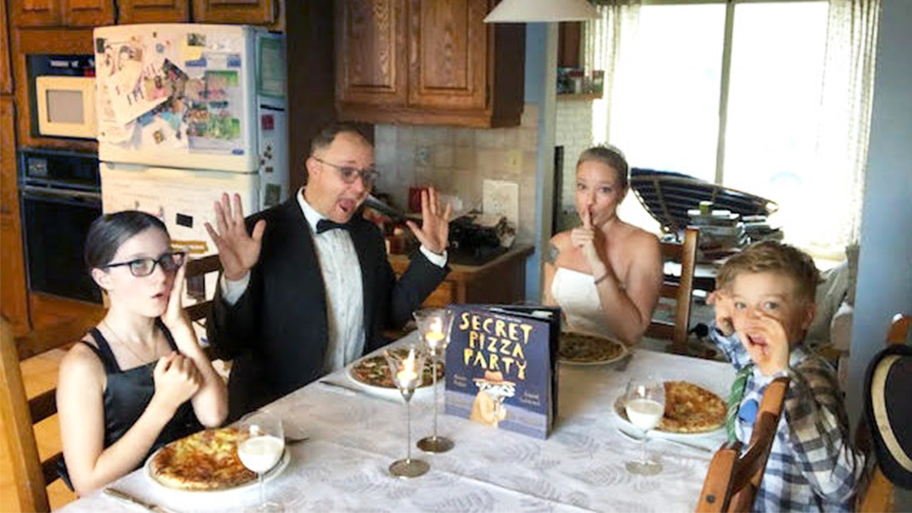 Photo of a family dressed up in fancy clothes at their dining table eating pizza