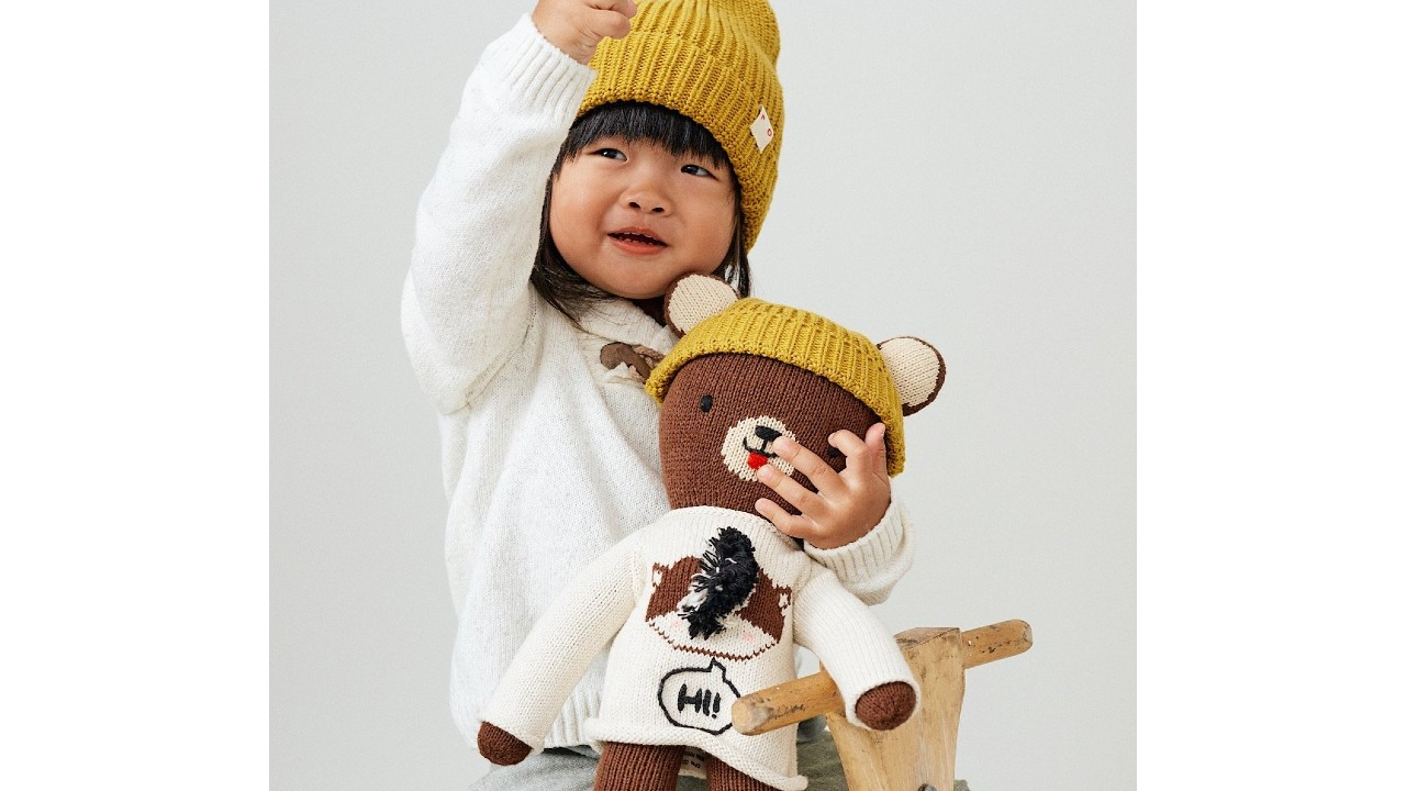 young girl holding bear with matching toque
