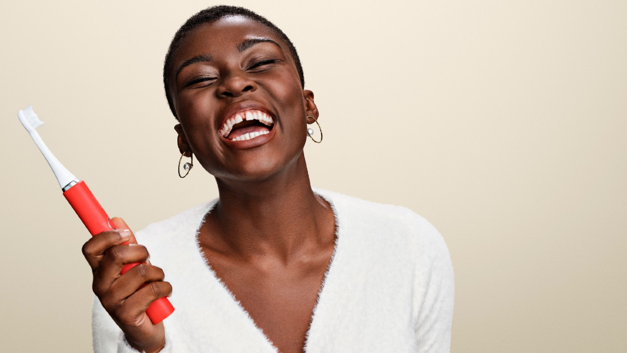 attractive woman smiling while holding red toothbrush