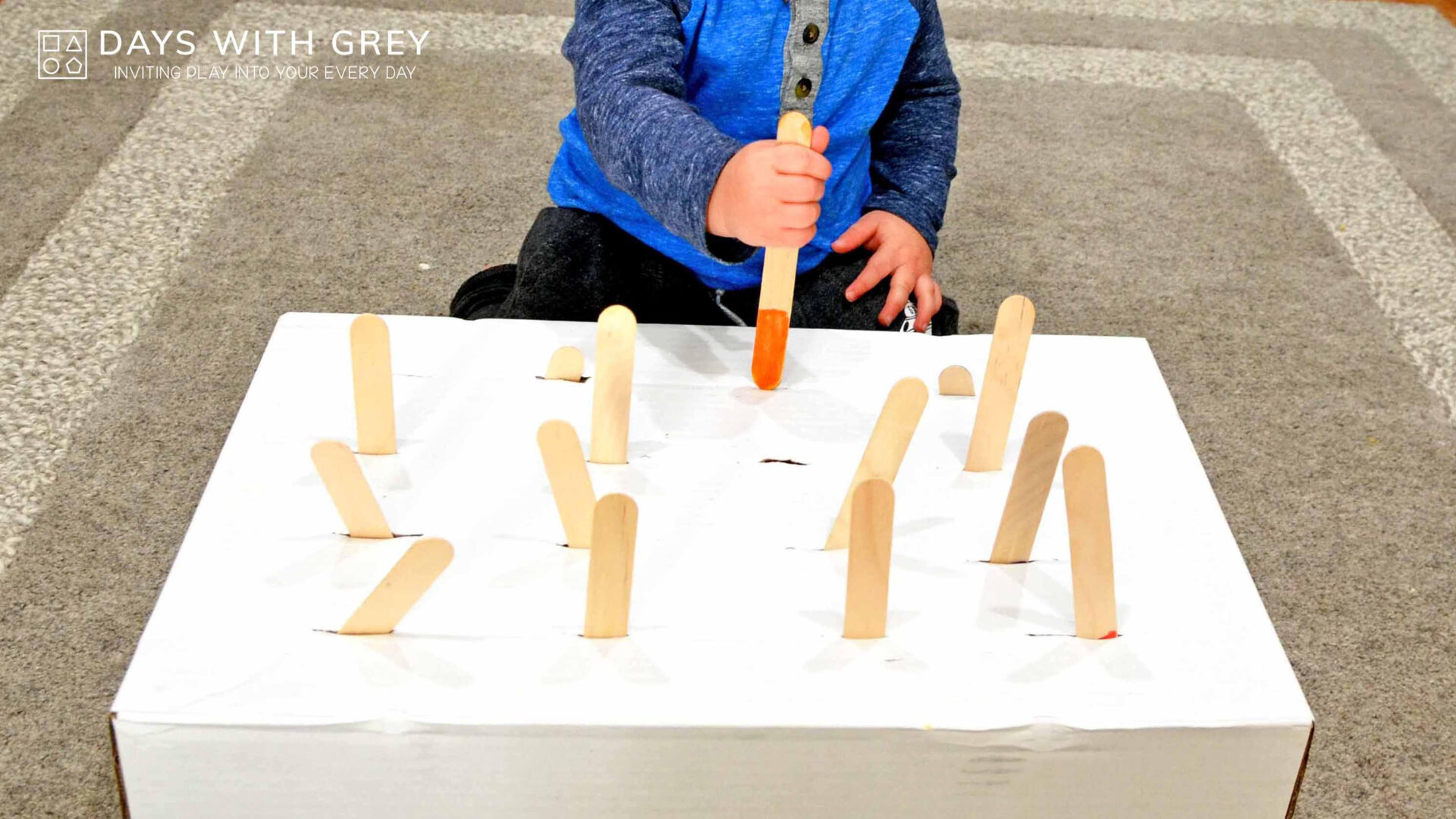 a child pokes popsicle sticks into a box with slits for a story on toddler activities you can set up the night before