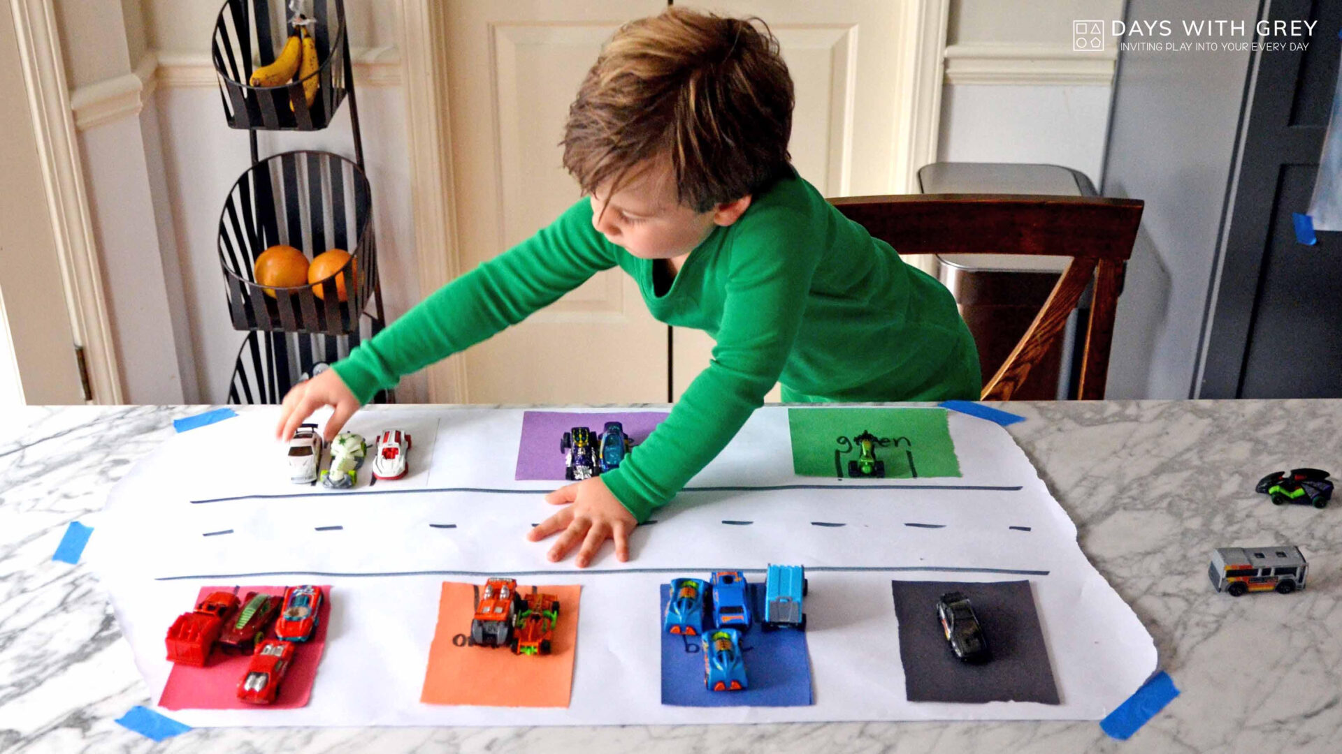 a young boy in a green shirt is putting different coloured cars in corresponding coloured parking lot squares for a story on toddler activities you can set up the night before