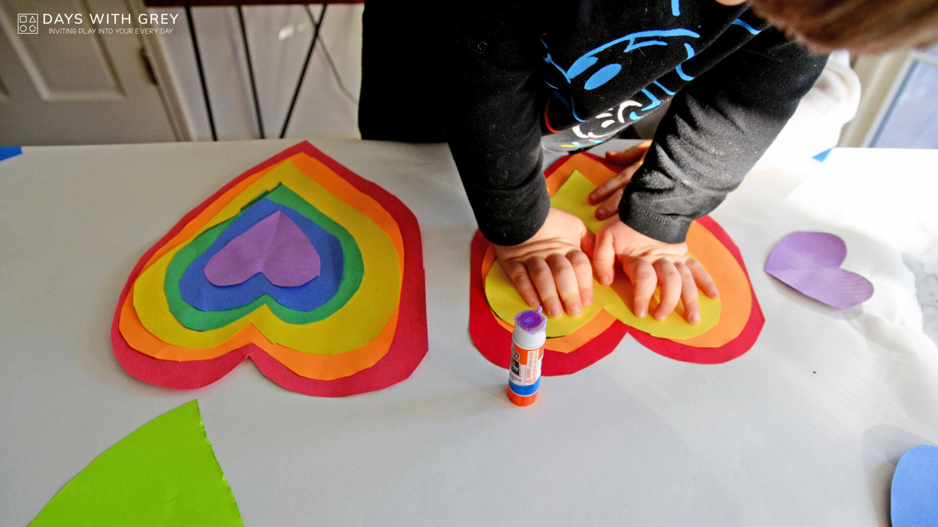 kids hands making a rainbow stack of hearts with paper cutouts for a story on toddler activities you can set up the night before