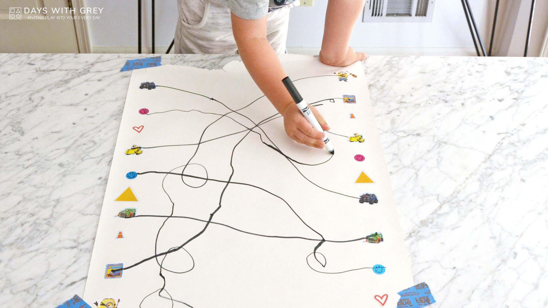 a child's hand draws lines between matching stickers on a bristol board for a story on toddler activities you can set up the night before