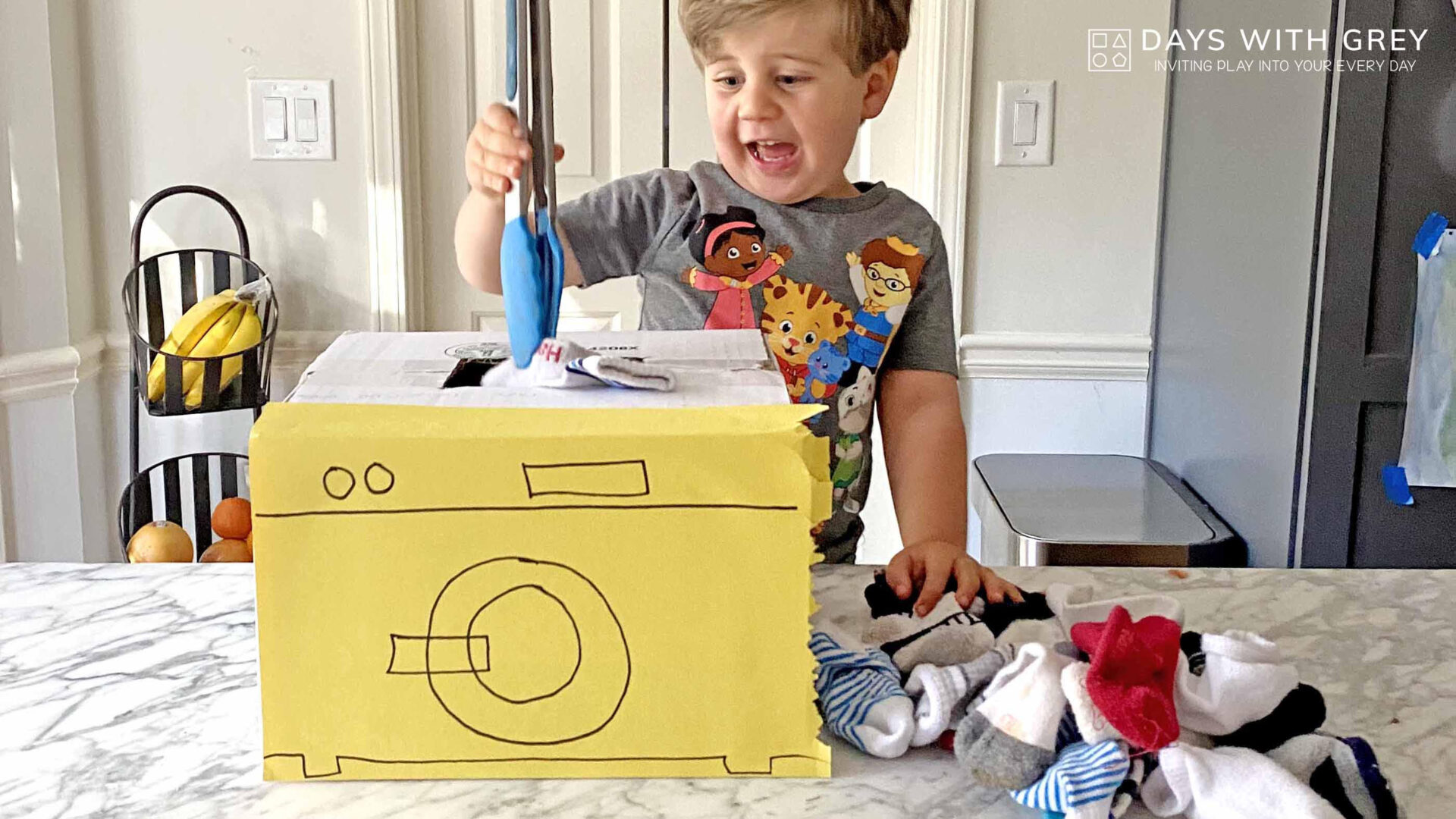 A young boy puts socks into a cardboard washing machine using tongs for a story on toddler activities you can set up the night before