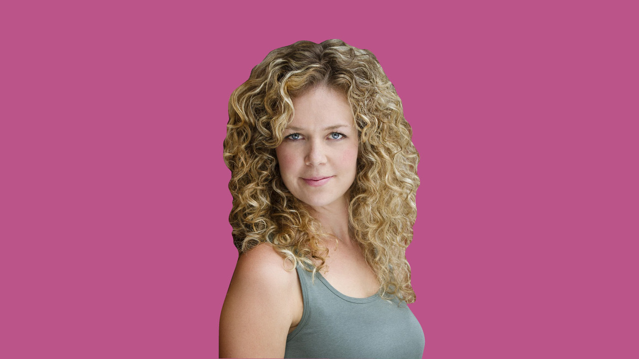 Workin' Moms star Juno Rinaldi wearing a grey tank top and posing in front of a pink background